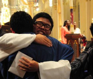 Lin hugs a member of the liturgical choir after the service. They lined up one by one to wish him well. He was all smiles.
